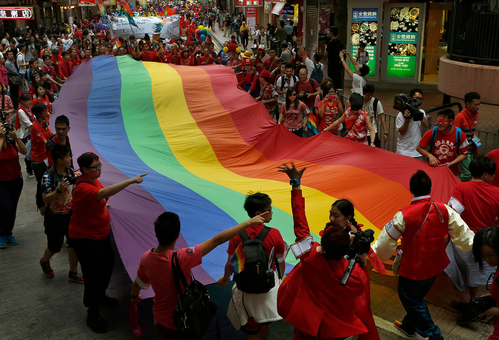 . Participants carry a rainbow flag, a symbol of the gay rights movement, during a gay rally in Hong Kong Saturday, Nov. 9, 2013. Organizers say thousands of people are taking part in the annual Gay Pride Parade including representatives from more than 50 organizations as well as participants from the mainland and Taiwan, according to government radio. (AP Photo/Vincent Yu)