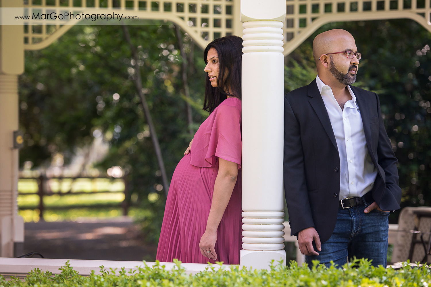 pregnant woman in pink dress and man in dark jacket looking in different directions under the gazebo in Ardenwood Historic Farm