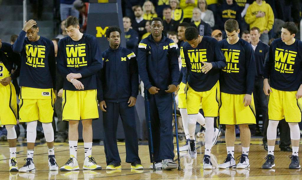 . Michigan guard Caris LeVert, center on crutches, stands with teammates before the first half of an NCAA college basketball game against Ohio State, Sunday, Feb. 22, 2015 in Ann Arbor, Mich.  (AP Photo/Carlos Osorio)