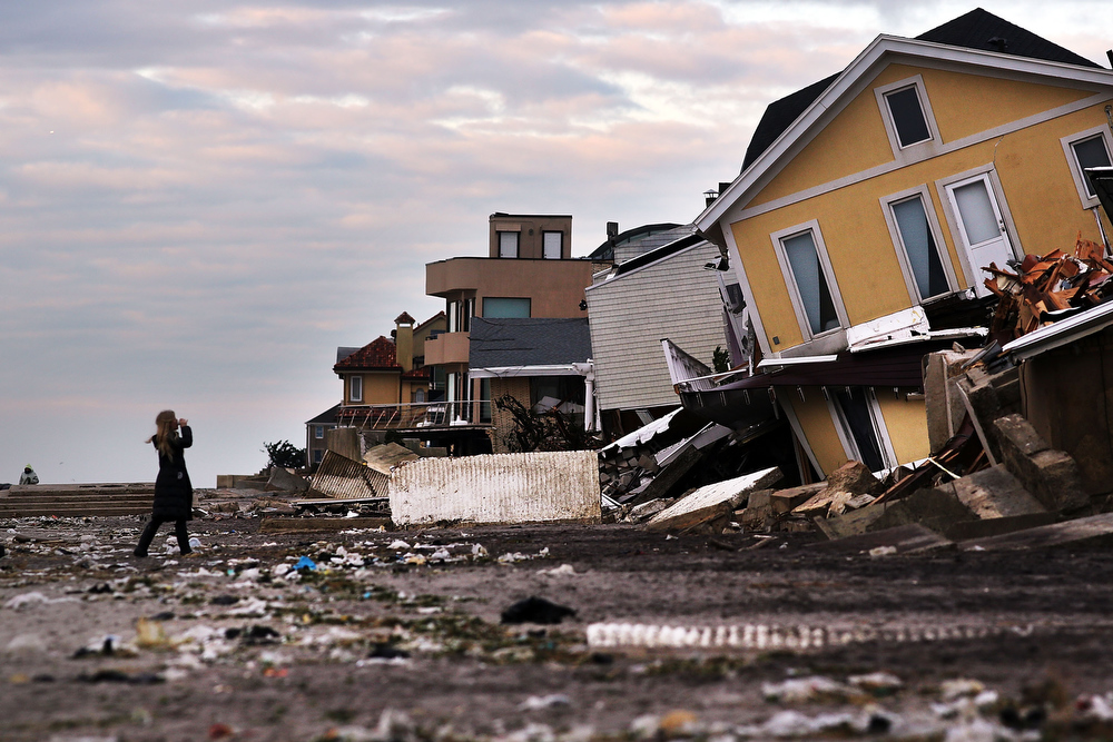 Description of . A woman walks along the beach in the heavily damaged Rockaway neighborhood, in Queens where a large section of the iconic boardwalk was washed away on November 2, 2012 in New York, United States. Limited public transit has returned to New York and most major bridges have reopened but will require three occupants in the vehicle to pass. With the death toll currently over 70 and millions of homes and businesses without power, the US east coast is attempting to recover from the effects of floods, fires and power outages brought on by superstorm Sandy.  (Photo by Spencer Platt/Getty Images)