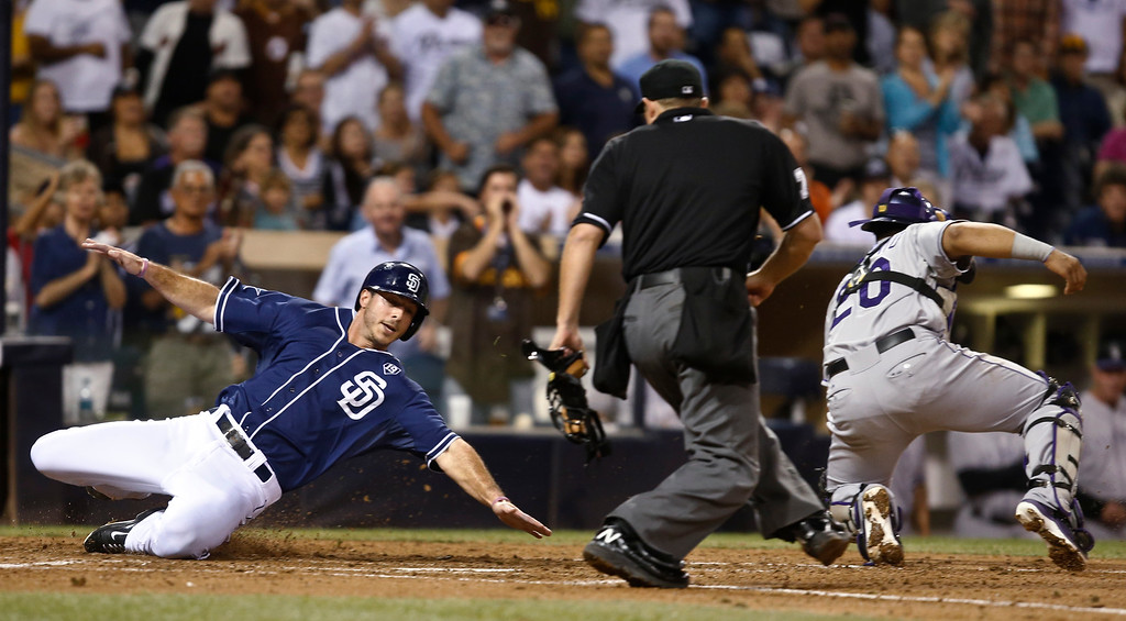 . San Diego Padres\' Tommy Medica reaches to touch home plate as Colorado Rockies catcher Wilin Rosario goes for the wide throw and umpire Tripp Gibson watches Medica score in the sixth inning of a baseball game Tuesday, Sept. 23, 2014, in San Diego.  (AP Photo/Lenny Ignelzi)