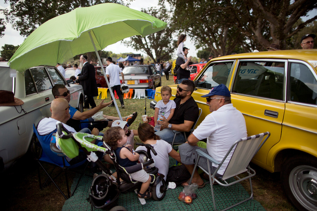 ". People sits next to their antique cars during the 31st annual ""Five Club\"" collectors car meeting in Ramat Gan, Israel, Friday, Oct. 6, 2017. (AP Photo/Oded Balilty)"