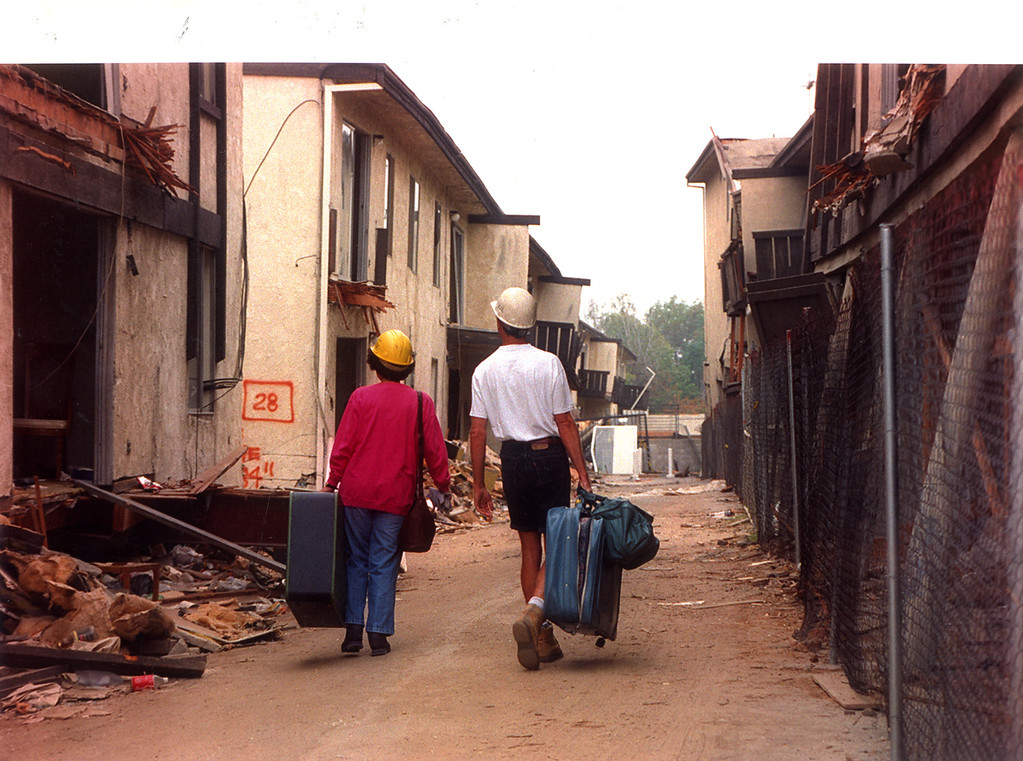 . Former tenants Joan DeWolf and Gary Benoit carry suitcases to salvage possessions from the Northridge Meadows Apartments.  July 15, 1994.  (Los Angeles Daily News file photo)