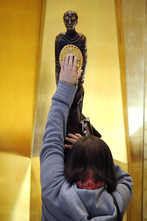 . A visitor touches the figure that holds a piece of Saint Juan Diego\'s famous cloak bearing the image of Our Lady of Guadalupe at the Cathedral of Our Lady of the Angels in Los Angeles, CA November 20, 2013.(Andy Holzman/Los Angeles Daily News)