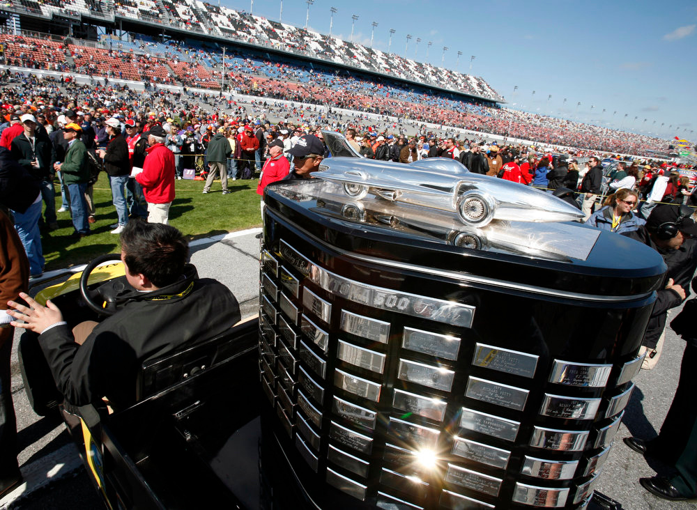. The Harvey J. Earl Trophy is moved through the crowd to the stage for pre-race activities at Daytona International Speedway in Daytona Beach, Fla., Sunday, Feb. 18, 2007. (AP Photo/Terry Renna)