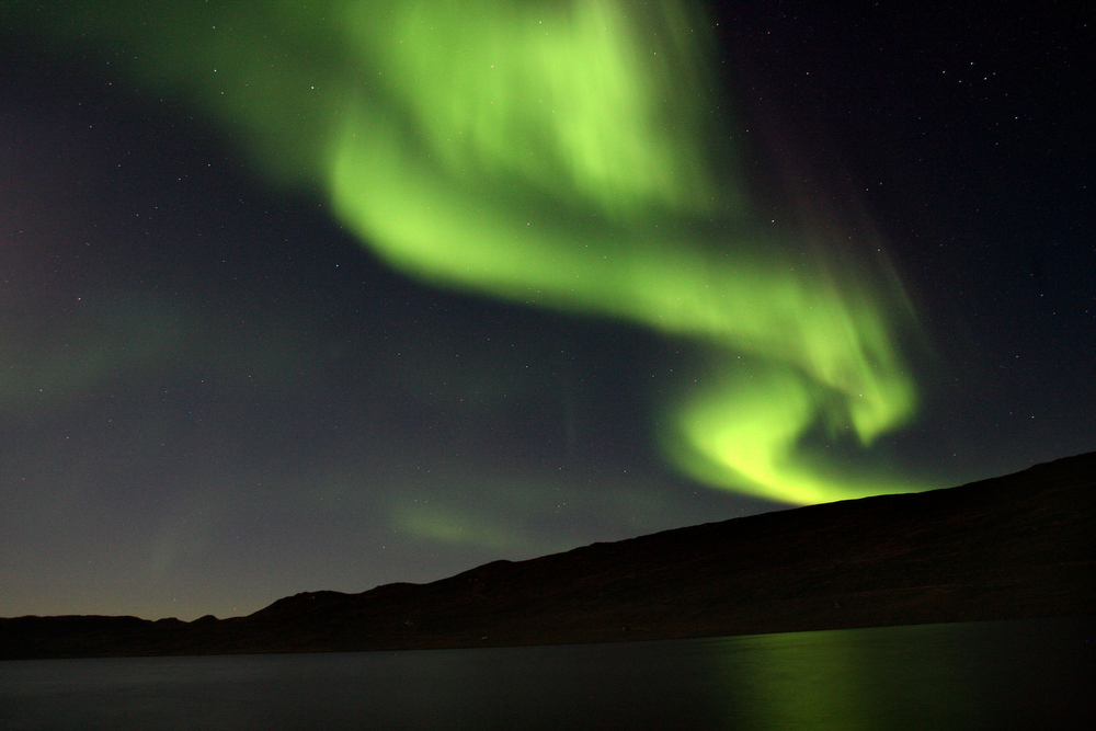 Description of . The Aurora Borealis glows over a lake September 02, 2007, near the Greenland town of Kangerlussuaq. The Northern Lights most often occurs from September to October and from March to April and are a popular tourist attraction.  (Photo by Uriel Sinai/Getty Images)