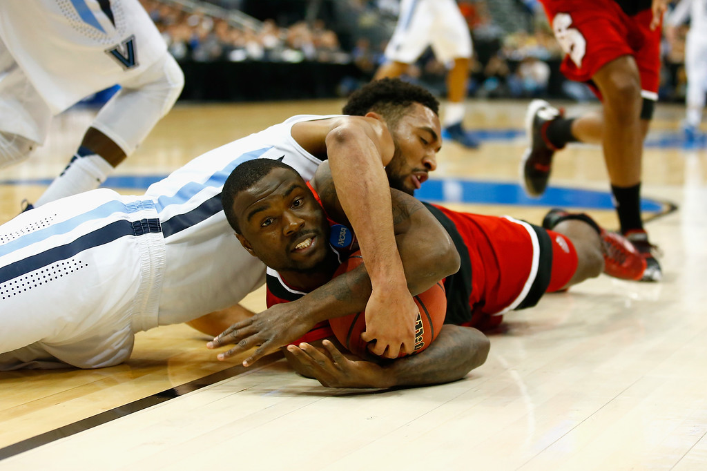 . Darrun Hilliard II #4 of the Villanova Wildcats and Desmond Lee #5 of the North Carolina State Wolfpack go after the ball in the first half during the third round of the 2015 NCAA Men\'s Basketball Tournament at Consol Energy Center on March 21, 2015 in Pittsburgh, Pennsylvania.  (Photo by Jared Wickerham/Getty Images)