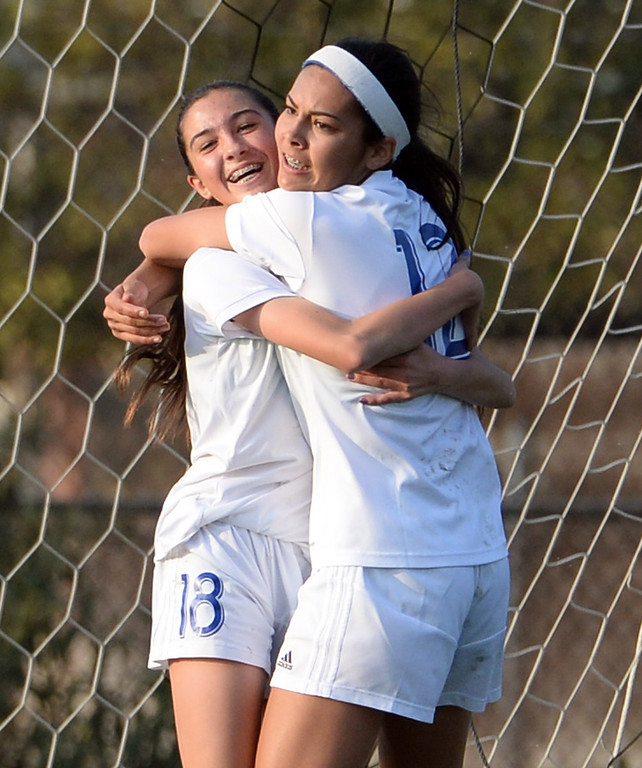 . Bishop Amat\'s Ashley Rushlow (18) is hugged by teammate Jamie Peters after scoring against Marshall in the first half of a prep soccer match at Bishop Amat High School in La Puente, Calif., on Thursday, Jan. 9, 2014.Amat won 3-0. (Keith Birmingham Pasadena Star-News)