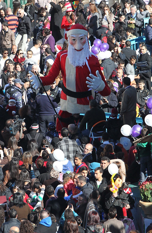 . Christian pilgrims gather near a Santa Claus dummy at Manger Square, outside the Church of the Nativity, traditionally believed to be the birthplace of Jesus Christ, during Christmas celebrations in the West Bank biblical town of Bethlehem on December 24, 2013.  Palestinian president Mahmud Abbas urged Christian pilgrims from around the world to visit the Holy Land to mark the visit of Pope Francis, set for 2014, in a Christmas message.  HAZEM BADER/AFP/Getty Images