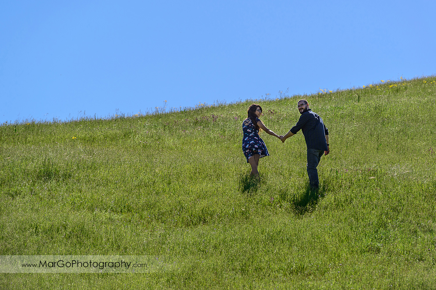 woman in blue dress and man in blue shirt holding hands and walking up the hill during engagement session at Sunol Regional Wilderness
