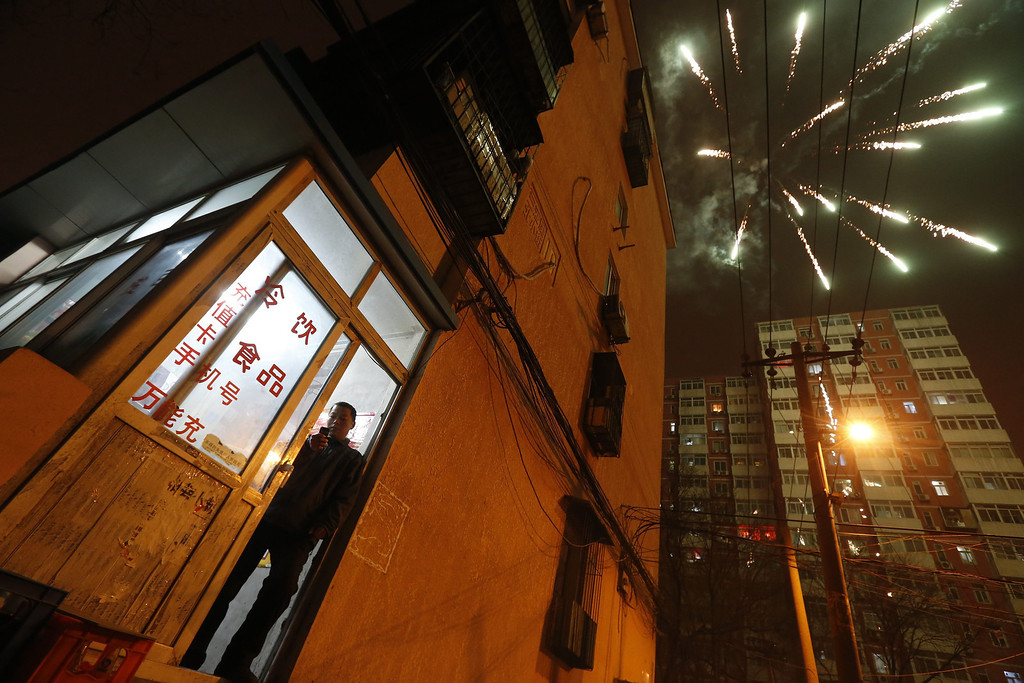 . A Chinese man stands at the building entrance of his home as fireworks explode in the sky minutes after midnight in Beijing, China, 31 January 2014.  EPA/ROLEX DELA PENA