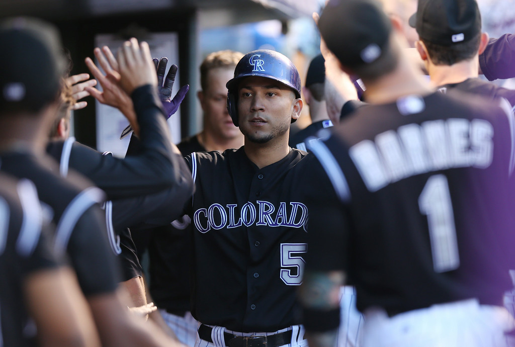 . Colorado Rockies\' Carlos Gonzalez, center, is congratulated by teammates after scoring on a triple by Corey Dickerson against the Chicago Cubs in the fourth inning of the Rockies\' 13-4 victory in a baseball game in Denver on Wednesday, Aug. 6, 2014. (AP Photo/David Zalubowski)