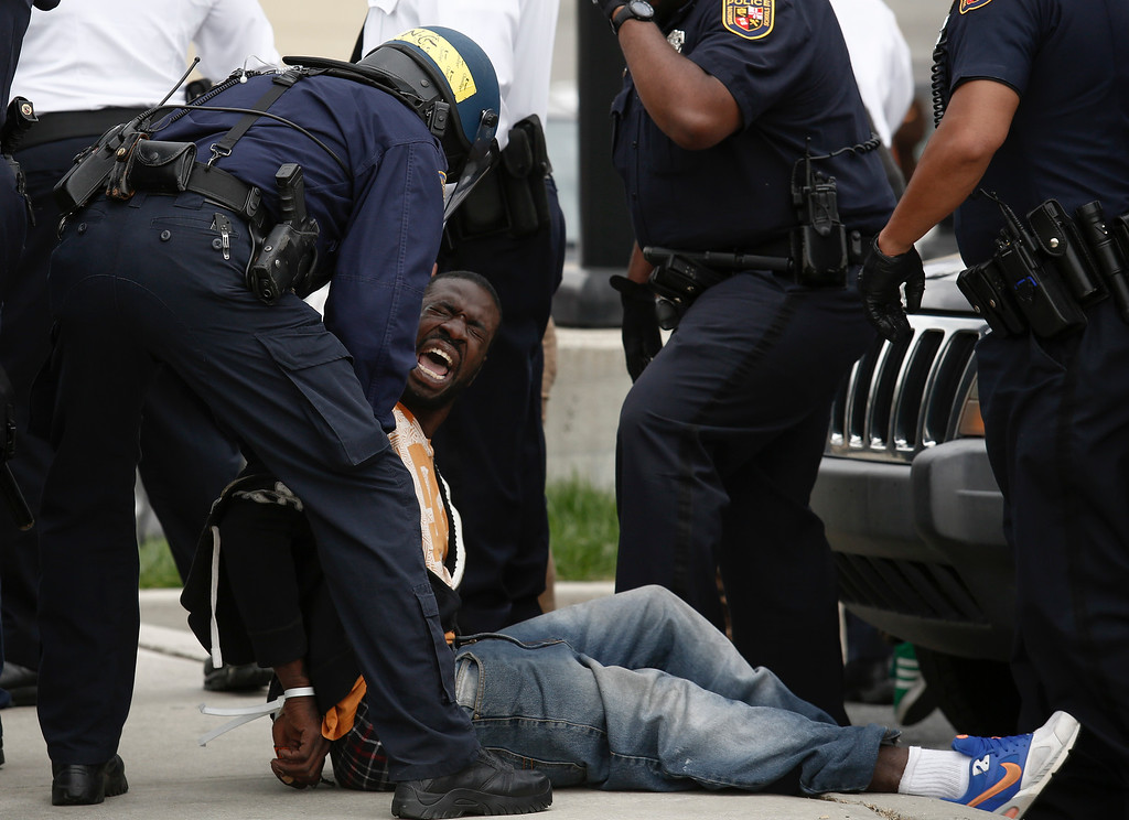 . BALTIMORE, MD - APRIL 27:  Baltimore Police officers arrest a man near Mowdamin Mall, April 27, 2015 in Baltimore, Maryland. The funeral service for Freddie Gray, who died last week while in Baltimore Police custody, was held on Monday morning. (Drew Angerer/Getty Images)