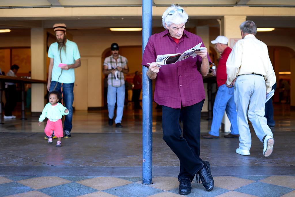 . People work on bets and walk through Santa Anita Park during the Breeders\' Cup in Arcadia Friday, November 1, 2013. (Photo by Sarah Reingewirtz/Pasadena Star-News)