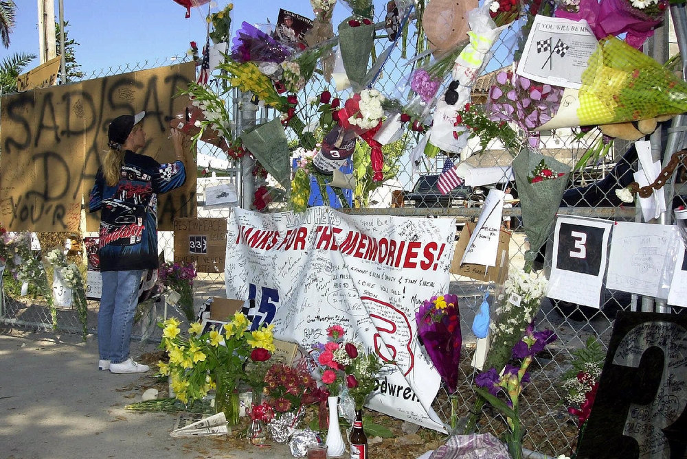 . Belina Yeatts, 31, of Palm Springs Fla., signs an message on a makeshift memorial in front of Dale Earnhardt\'s home, which is under construction in Palm Beach Gardens, Fla., Wednesday, Feb. 21, 2001. Earnhardt, 49, was killed Sunday when his Chevrolet hit the wall in the final lap of the Daytona 500. (AP Photo/Steve Mitchell)
