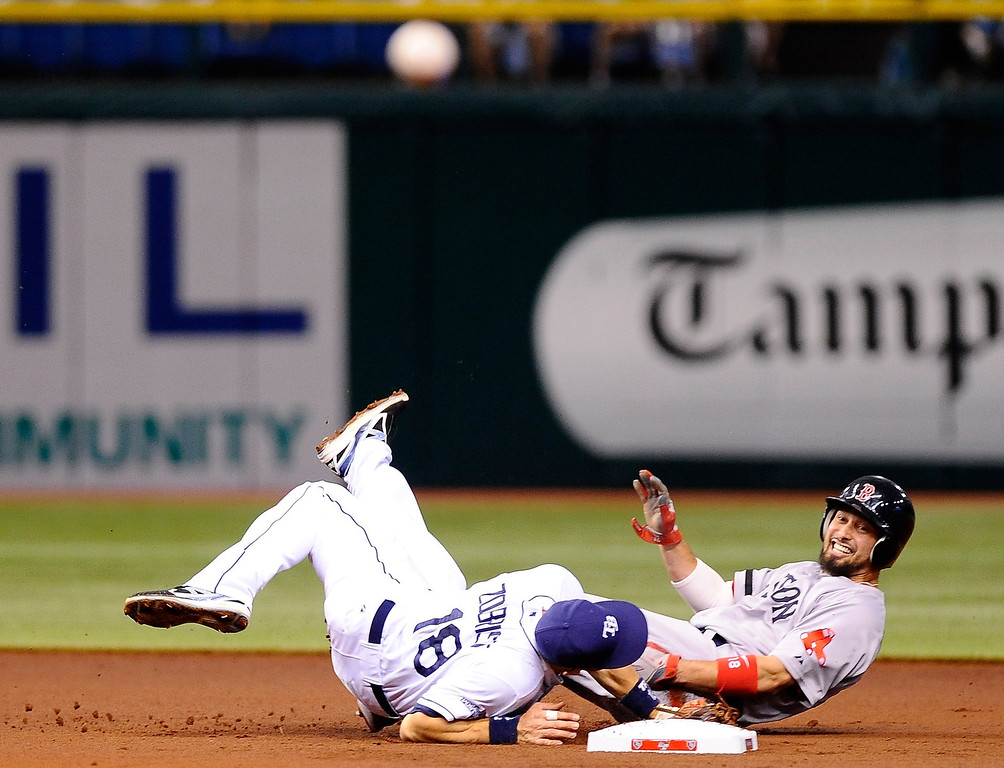 . Ben Zobrist #18 of the Tampa Bay Rays falls after colliding with Shane Victorino #18 of the Boston Red Sox and committing a throwing error to first base in the first inning during Game Three of the American League Division Series at Tropicana Field on October 7, 2013 in St Petersburg, Florida.  (Photo by Brian Blanco/Getty Images)
