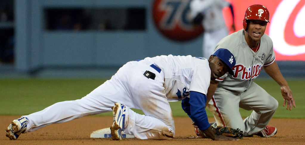 . Los Angeles Dodgers second baseman Dee Gordon (9) looks toward first base after forcing out Philadelphia Phillies\' Ben Revere at second base in the second inning of a baseball game on Tuesday, April 22, 2013 in Los Angeles.   (Keith Birmingham/Pasadena Star-News)