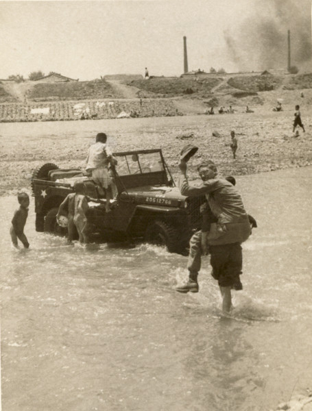 Reedie catching a ride across the river while local kids wash a GI vehicle