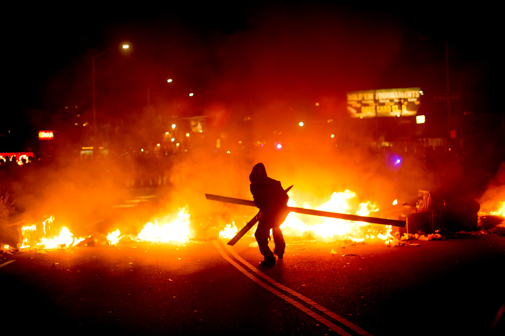 . A protester adds wood to a fire burning in Oakland, Calif., on Tuesday, Nov. 25, 2014, a day after the announcement that a grand jury decided not to indict Ferguson police officer Darren Wilson in the fatal shooting of Michael Brown. Protesters briefly shut down two major freeways, vandalized police cars and looted businesses in downtown Oakland, smashing windows at cell phone stores, car dealerships, restaurants and convenience stores on a second night of protests. (AP Photo/Noah Berger)