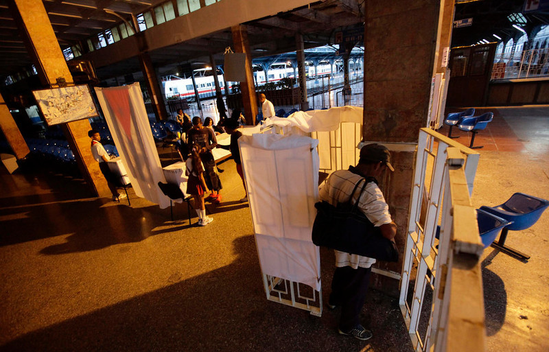 . A man prepares his ballot papers in a voting booth at a special polling station set up in Havana\'s main train station February 3, 2013. Cubans go to polls to elect National Assembly representatives. REUTERS/Desmond Boylan