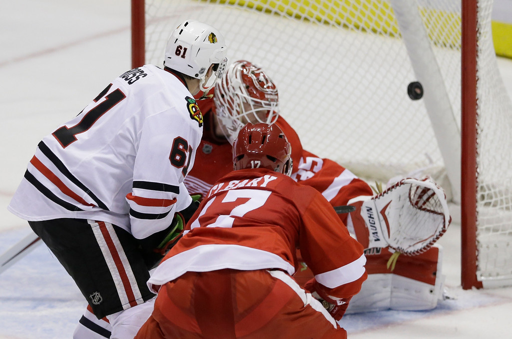 . Chicago Blackhawks left wing Garret Ross (61) shoots the puck past Detroit Red Wings goalie Jimmy Howard for a goal during the third period of an NHL hockey game in Detroit, Thursday, Sept. 25, 2014. (AP Photo/Carlos Osorio)