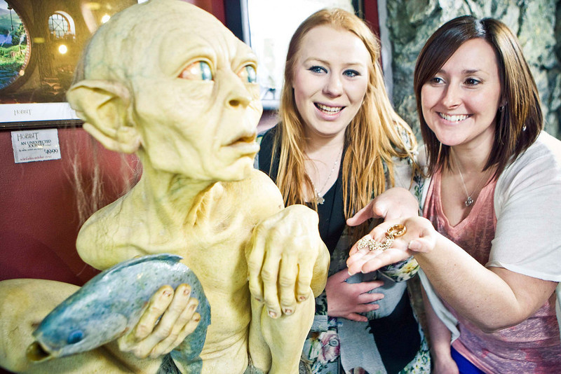 . Visitors pose next to a sculpture of the J. R. R. Tolkien character Gollum at the Weta Cave museum in Wellington in this September 25, 2012 handout photograph. New Zealand\'s capital city was rushing to complete its transformation into a haven for hairy feet and pointed ears on November 27, 2012 as stars jetted in for the long-awaited world premiere of the first movie of the Hobbit trilogy. Picture taken September 25, 2012. REUTERS/Positively Wellington Tourism/Handout
