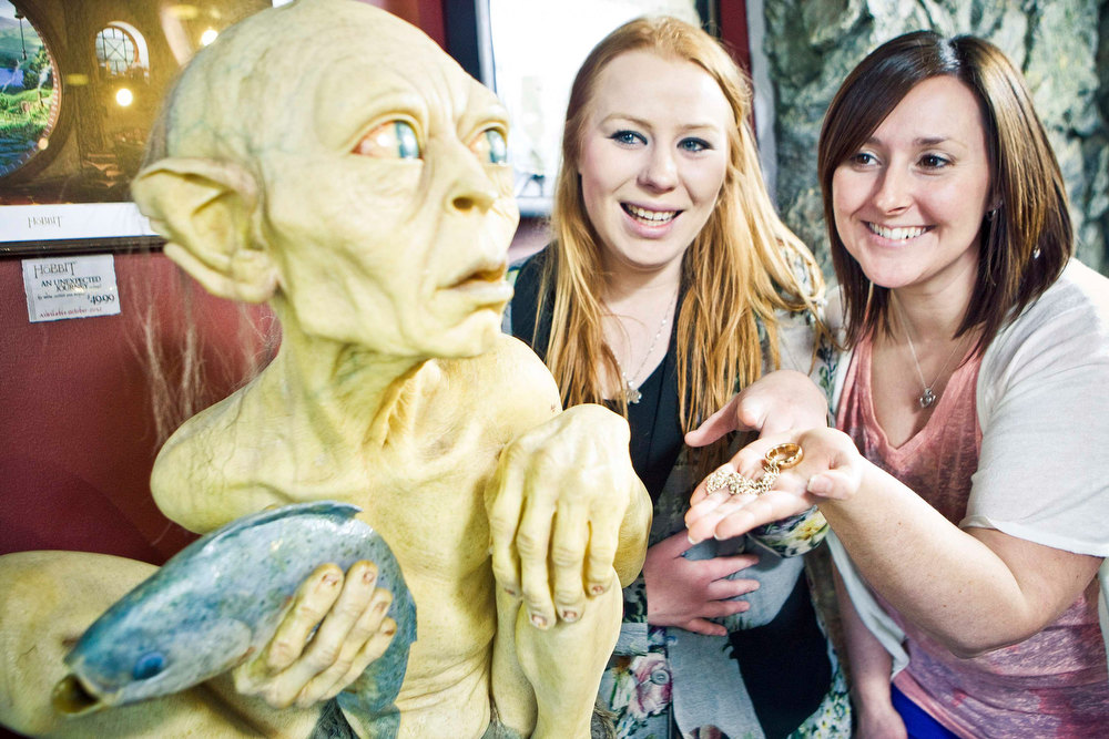Description of . Visitors pose next to a sculpture of the J. R. R. Tolkien character Gollum at the Weta Cave museum in Wellington in this September 25, 2012 handout photograph. New Zealand's capital city was rushing to complete its transformation into a haven for hairy feet and pointed ears on November 27, 2012 as stars jetted in for the long-awaited world premiere of the first movie of the Hobbit trilogy. Picture taken September 25, 2012. REUTERS/Positively Wellington Tourism/Handout