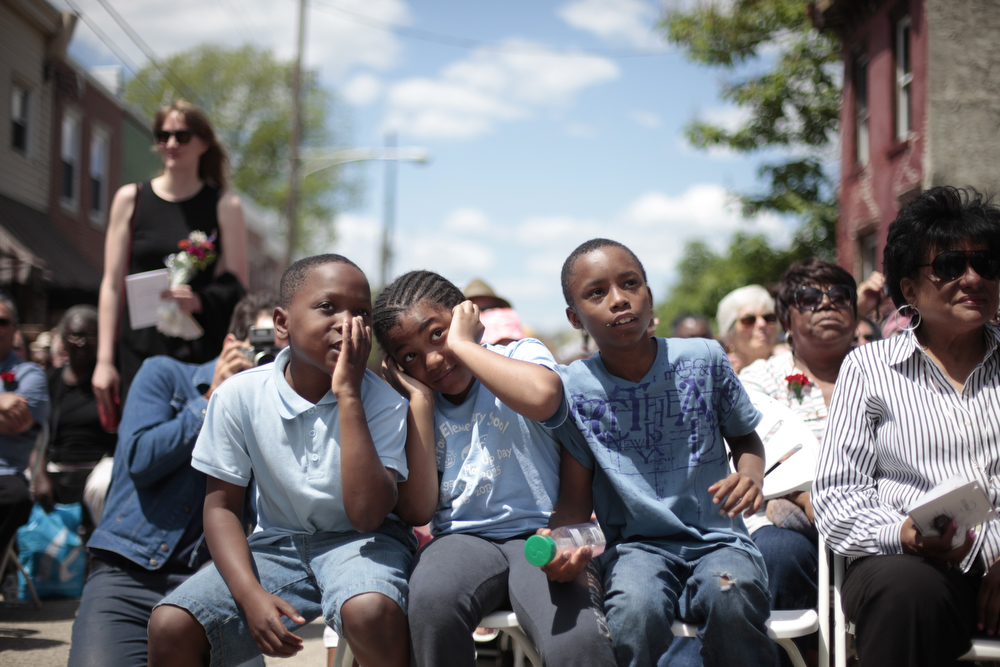"""Description of . From left, Jason Jackson, 8, Myla Gunn, 7, and Garis Harris, 10, watch as an abandoned home is demolished in the impoverished Mantua section Philadelphia on Saturday, May 31, 2014. The cultural and memorial project called """"Funeral for a Home"""" celebrated the dilapidated row house's colorful life before it was knocked down. Organizers from Temple University said it was an effort to commemorate neighborhood history in a city where about 600 houses are torn down each year and 25,000 others sit vacant. (AP Photo/Jessica Kourkounis)"""