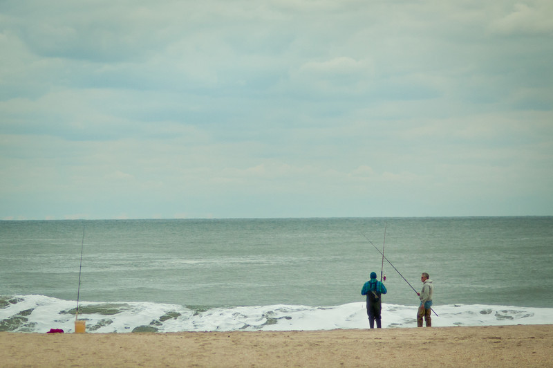 A man in a blue shirt with fishing pants on holding a fishing rod standing next to a man in a tan sweatshirt with fishing pants on also holding a rod both fishing in the ocean by Alex Kaplan, photographer http://www.alexkaplanphoto.com