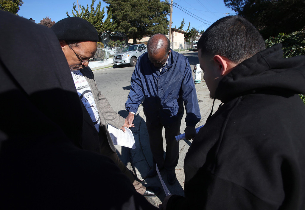 . Donald Paul Miller, left, and Ben Darden, center, of Allen Temple Baptist Church, pray with Alberto, 19, at a homicide scene on 94th Avenue and Hillside Street in Oakland, Calif. on Saturday, Jan. 12, 2013. Miller, Darden, and others do community outreach immediately after homicides in Oakland. Ken Harbin, 17, who lived nearby, was shot and killed there on Friday night about 8:15 p.m. according to Oakland police. Harbin was a friend of Alfredo. There were four homicides in six hours on Friday in Oakland.  (Jane Tyska/Staff)