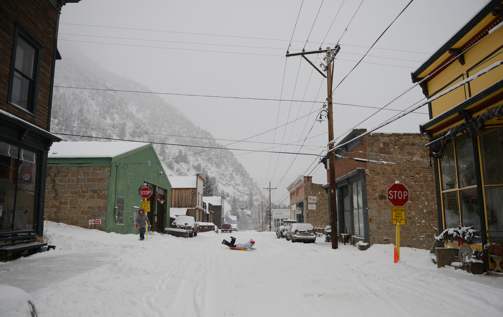 . Casey Boder, 16, center, sleds down Silver Street in historic downtown Silver Plume, Tuesday, December 18, 2012, as Sarah Street, left, walks downtown. Snow continues to falls though out much of the day in the area.  RJ Sangosti, The Denver Post