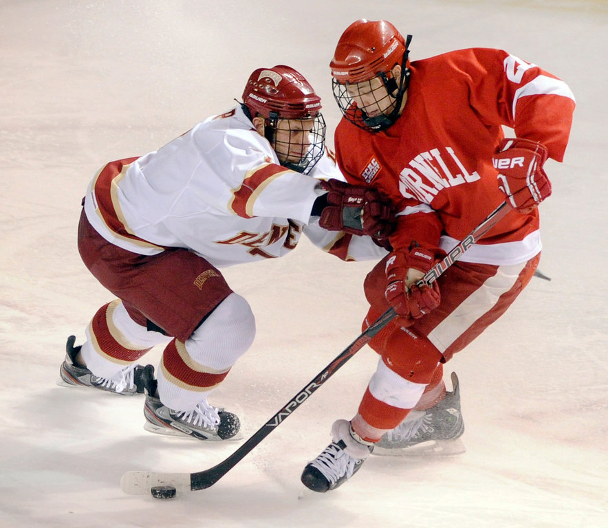 . Cornell centr Dustin Mowrey (20) tried to skate past Denver defenseman Paul Phillips (7) in the second period. The University of Denver hockey team hosted Cornell at Magness Arena Saturday night, January 5, 2013. Karl Gehring/The Denver Post
