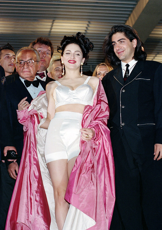 ". American singer-actress Madonna leaves the screening of her movie ""In Bed with Madonna,\"" known as \""Truth or Dare\"" in the United States, with director Alek Keshishian, right, at the 44th Cannes Film Festival in France, May 14, 1991.  The documentary, filmed by the 26-year-old Harvard graduate, chronicles Madonna\'s 1990 \""Blond Ambition\"" tour.  (AP Photo/Gilbert Tourte)"