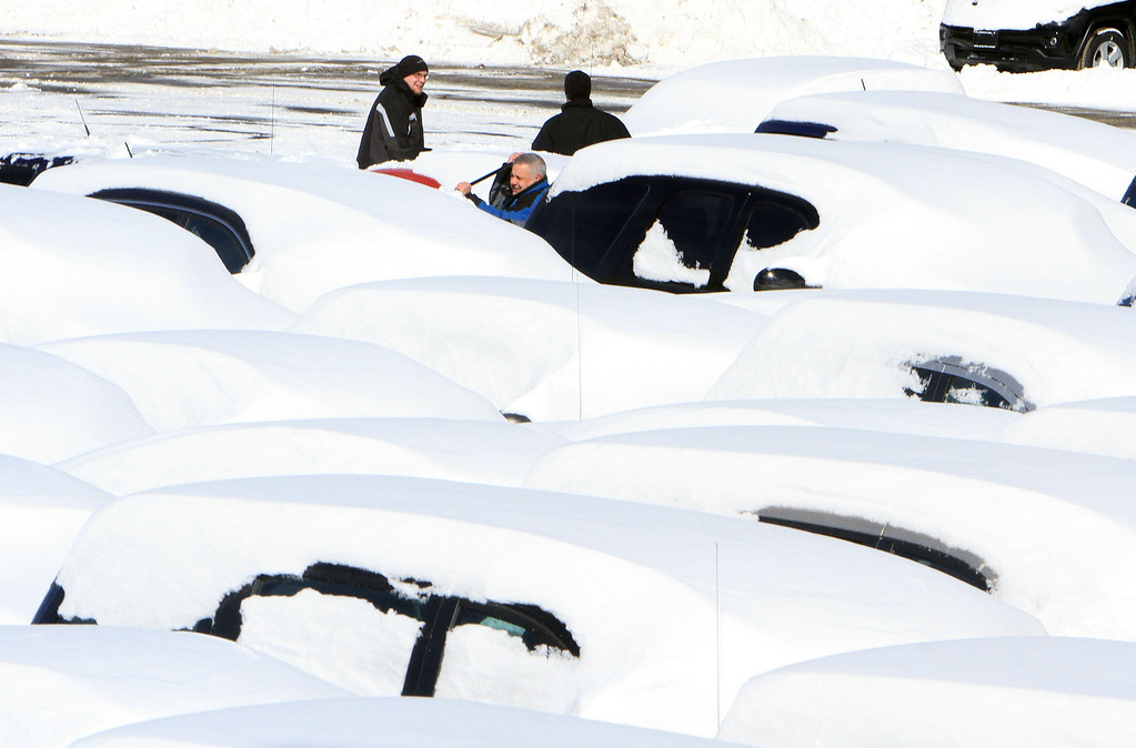 . Workers at a car dealership on Route 6 in Carmel, N.Y. clean snow from the cars in their lot, Saturday, Feb. 9, 2013. The year\'s first major winter storm dumped up to 21 inches on the Lower Hudson Valley.  (AP Photo/The Journal News, Frank Becerra Jr.)