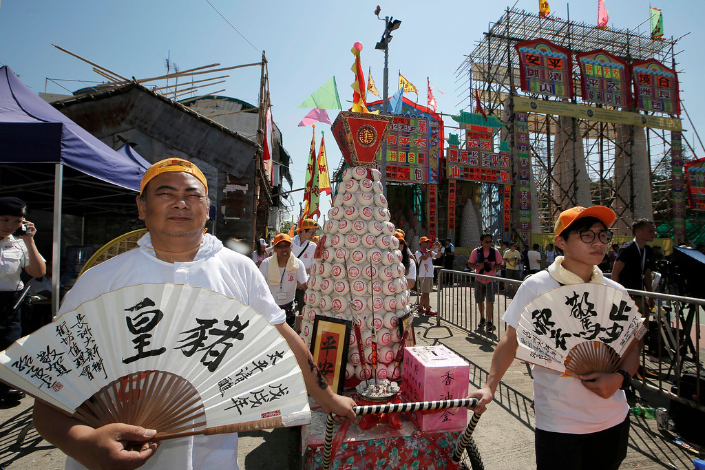 . Villagers carry a bun tower during a parade on the outlying Cheung Chau island in Hong Kong to celebrate the Bun Festival Tuesday, May 22, 2018. Bun Festival, the Taoist God of the Sea, is worshipped and evil spirits are scared away by loud gongs and drums during the procession. The celebration includes bun scrambling, parades, opera performances, and children dressed in colorful costumes. (AP Photo/Kin Cheung)