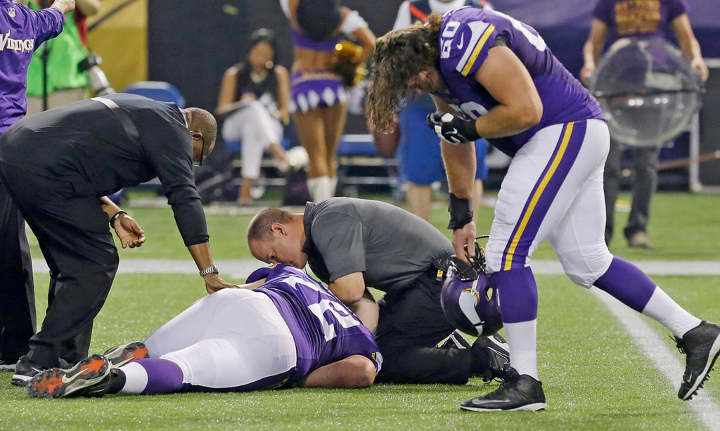 . Vikings offensive guard Jeff Baca, right, reacts as trainers assist injured guard Seth Olsen, center, during the second quarter. (AP Photo/Jim Mone)