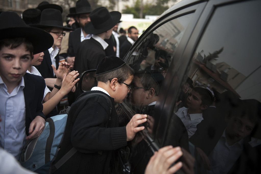 . A child looks inside the car of an important Rabbi as Ultra-Orthodox Jews take part in a mass prayer vigil in Jerusalem on March 2, 2014 in protest at plans to conscript young ultra-Orthodox men for Israeli military or civilian service. Hundreds of thousands of ultra-Orthodox Jews representing the three major streams -- Lithuanian, Hassidic and Sephardi -- were united in a show of force against impending legislation that could change their legal status in the Jewish state.  DAVID BUIMOVITCH/AFP/Getty Images