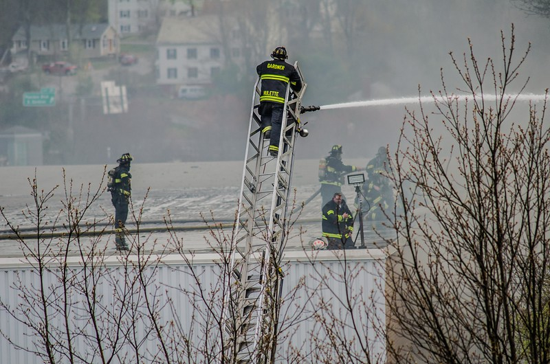 Gardner FF Eric Hulette operates a ladder pipe from the top of Gardner Combination 4 at the rear of the building during a 6 Alm fire.