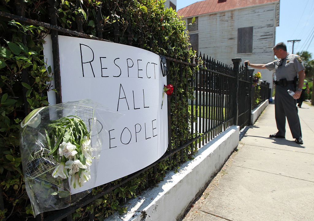 . A law enforcement officer clears the Morris Brown AME Church for safety reasons during a prayer vigil for the victims of Wednesday\'s shooting at Emanuel AME Church in Charleston, S.C., on Thursday, June 18, 2015.  Dylann Storm Roof, 21, was arrested Thursday in the slayings of several people, including the pastor, at a prayer meeting inside the historic black church. (Curtis Compton /Atlanta Journal-Constitution via AP)