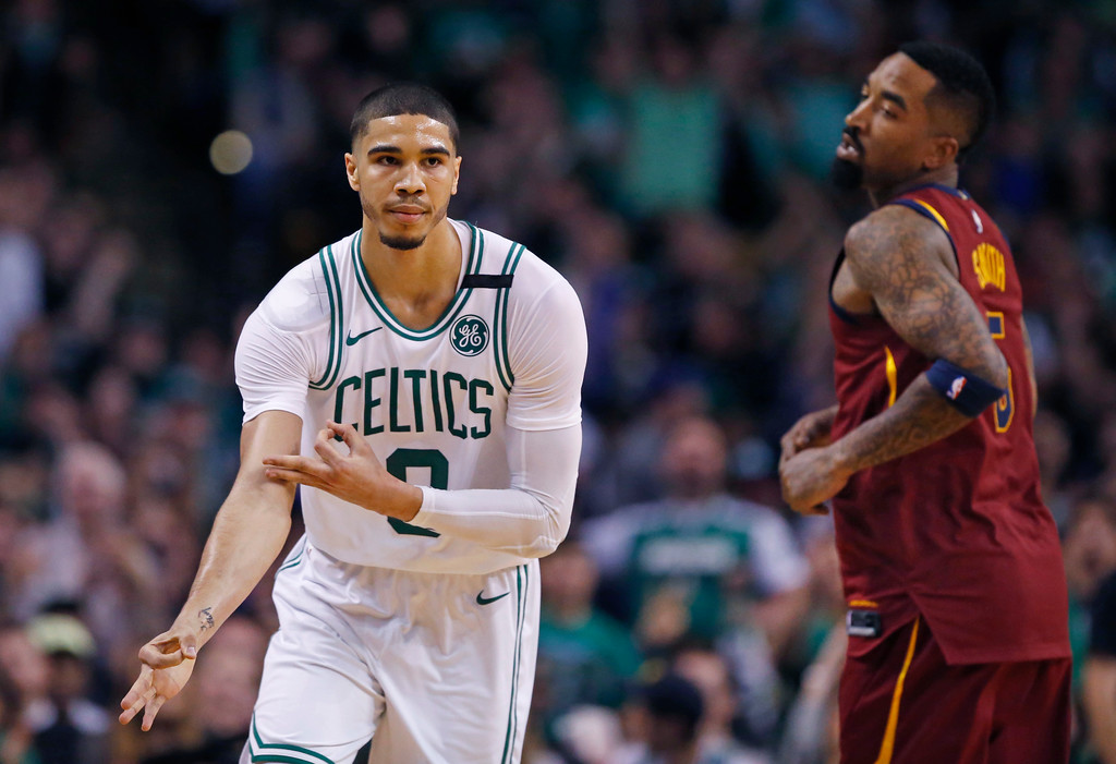 . Boston Celtics forward Jayson Tatum (0) celebrates his three-point basket as Cleveland Cavaliers guard JR Smith (5) looks on during the second quarter of Game 1 of the NBA basketball Eastern Conference Finals, Sunday, May 13, 2018, in Boston. (AP Photo/Michael Dwyer)