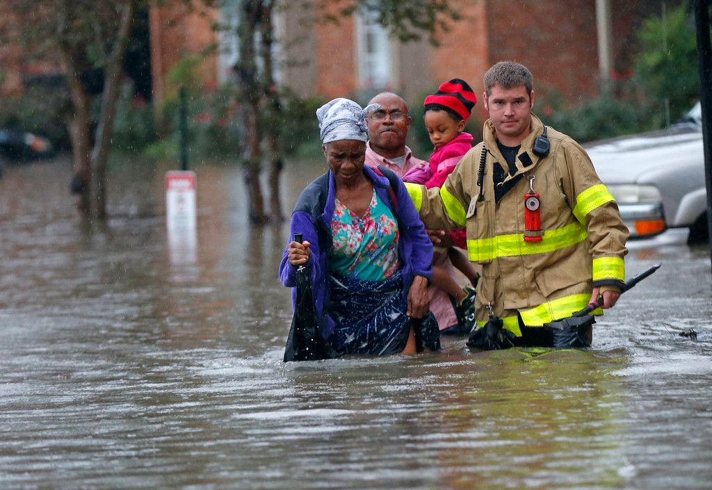 . A member of the St. George Fire Department assists residents as they wade through floodwaters from heavy rains in the Chateau Wein Apartments in Baton Rouge, La., Friday, Aug. 12, 2016. (AP Photo/Gerald Herbert)