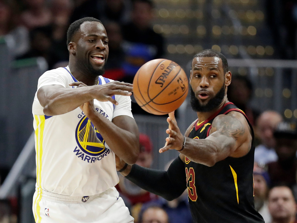 . Golden State Warriors\' Draymond Green, left, passes against Cleveland Cavaliers\' LeBron James in the first half of an NBA basketball game, Monday, Jan. 15, 2018, in Cleveland. (AP Photo/Tony Dejak)