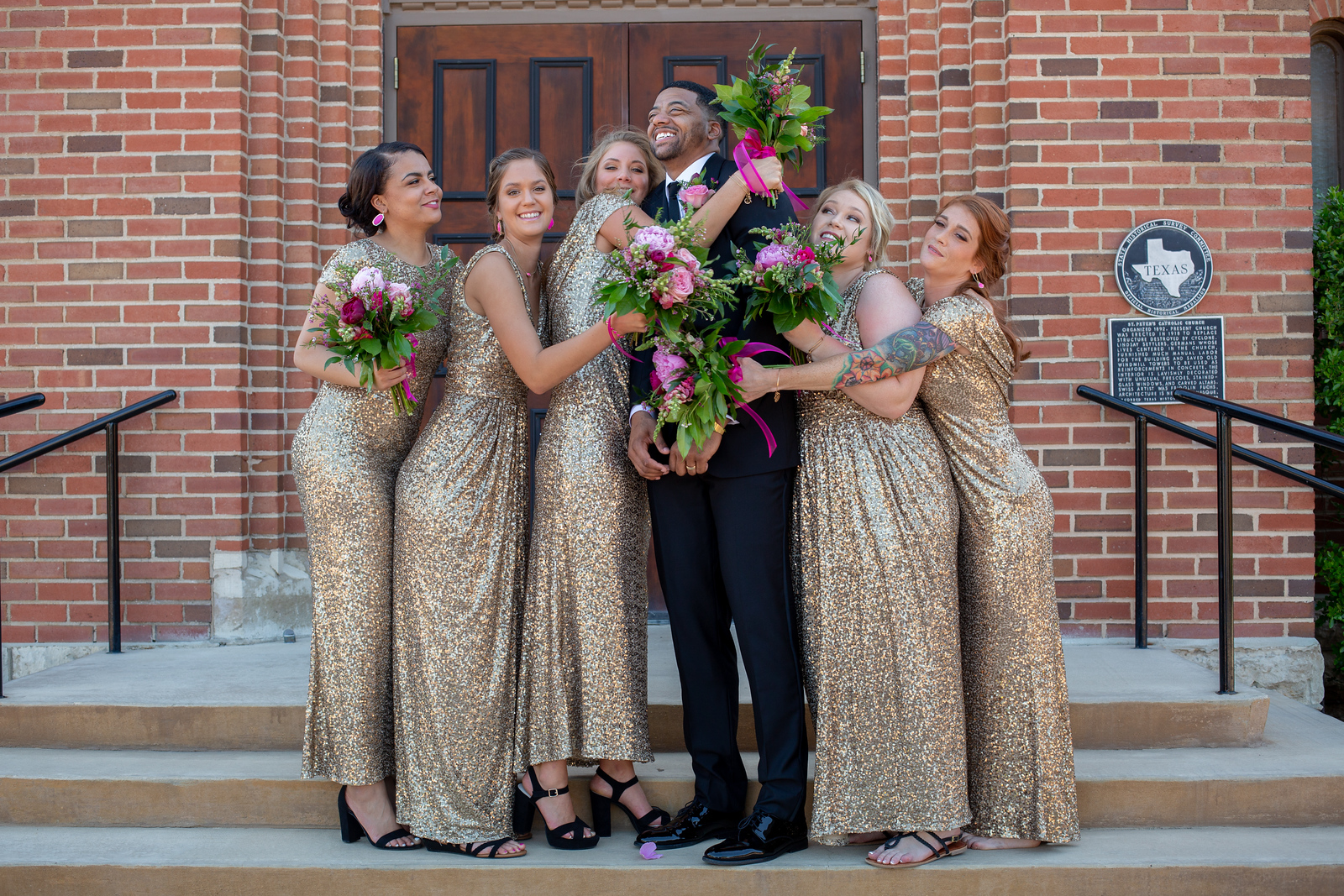 five bridesmaids wearing gold dresses all hugging the groom