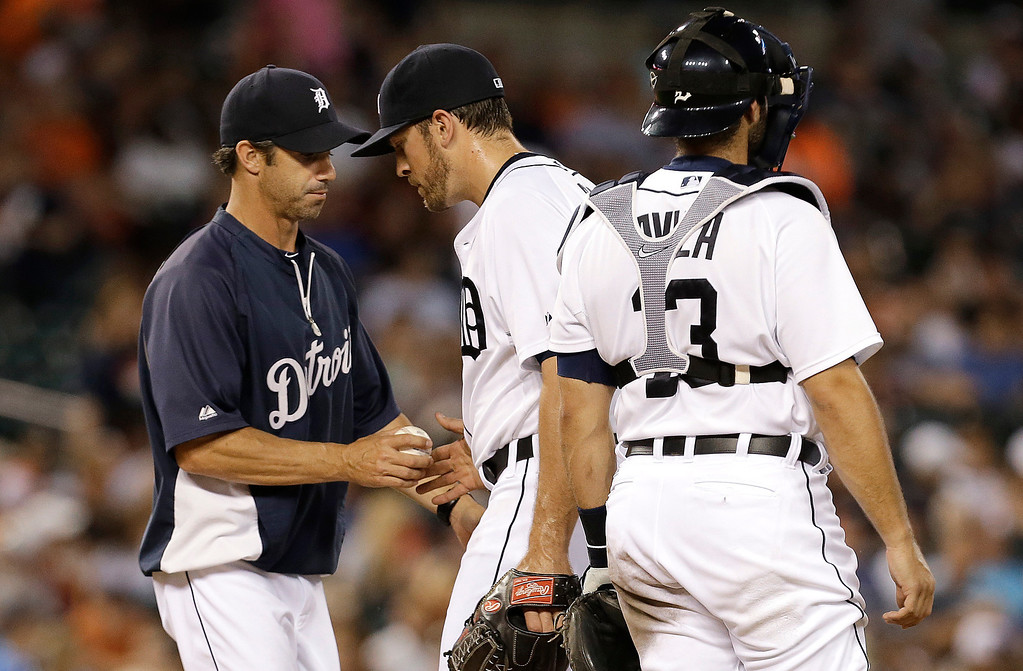 . Detroit Tigers manager Brad Ausmus, left, takes the ball from Evan Reed as catcher Alex Avila (13) looks on against the Kansas City Royals in the seventh inning of a baseball game in Detroit, Monday, June 16, 2014.  (AP Photo/Paul Sancya)