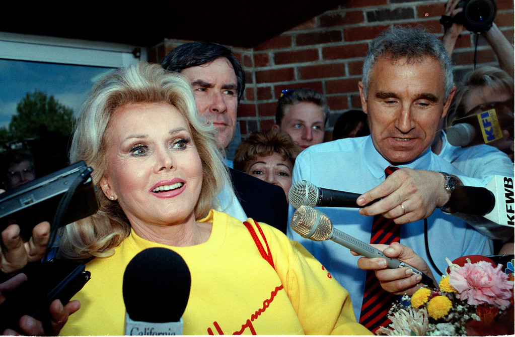. In this July 31, 1990 file photo, Zsa Zsa Gabor, accompanied by her husband Frederick Prinz von Anhalt, right, is surrounded by media upon her release from jail in El Segundo, Calif.  (AP Photo/Nick Ut, File)