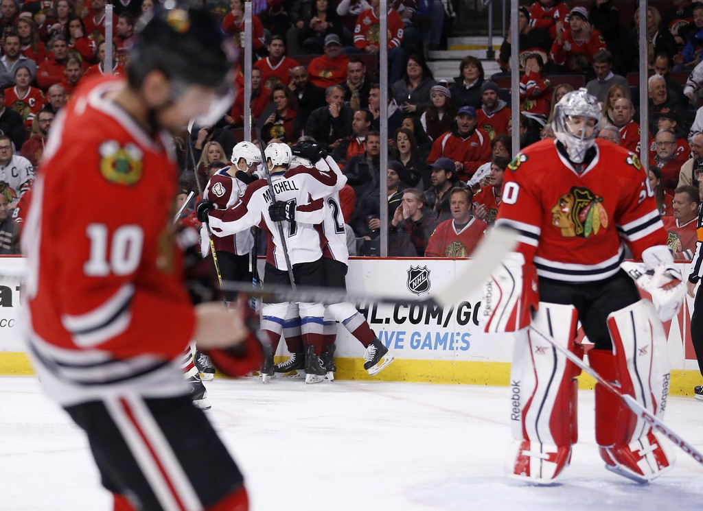 . The Colorado Avalanche celebrate Maxime Talbot\'s goal as Chicago Blackhawks left wing Patrick Sharp (10) and Corey Crawford skate away during the first period of an NHL hockey game Tuesday, Jan. 6, 2015, in Chicago. (AP Photo/Charles Rex Arbogast)