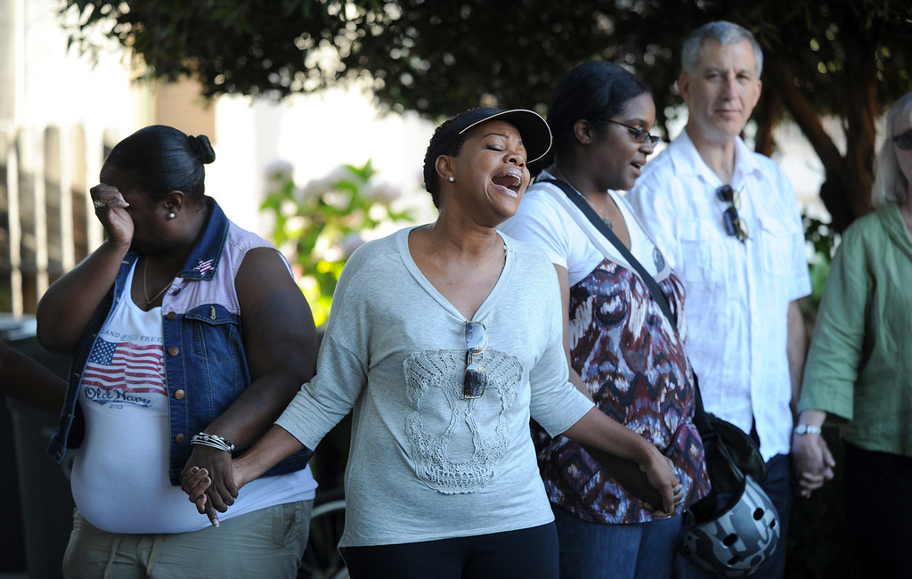 . Stacy Hogg leads a prayer circle with a song during a prayer vigil on the 3400 block of Wilson Ave. in Oakland, Calif., on Thursday, July 18, 2013. One young girl was killed and 3 other people were wounded when an unknown gunman fired shots through the door of the apartment on Wilson Avenue. (Dan Honda/Bay Area News Group)