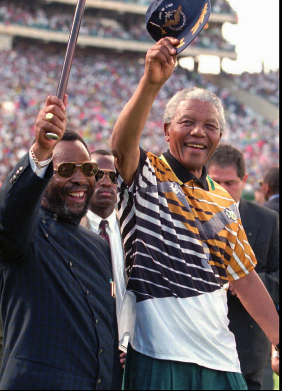 . South African President Nelson Mandela, right, and Zulu King Goodwill Zwelethini, left, greet the crowd prior to the African Nations Cup final in Johannesburg Saturday, February 3, 1996. South Africa beat Tunisia 2-0 in the final. (AP Photo/Adil Bradlow)