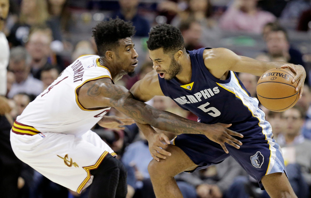 . Memphis Grizzlies\' Andrew Harrison (5) drives past Cleveland Cavaliers\' Iman Shumpert (4) in the first half of an NBA basketball game Tuesday, Dec. 13, 2016, in Cleveland. (AP Photo/Tony Dejak)