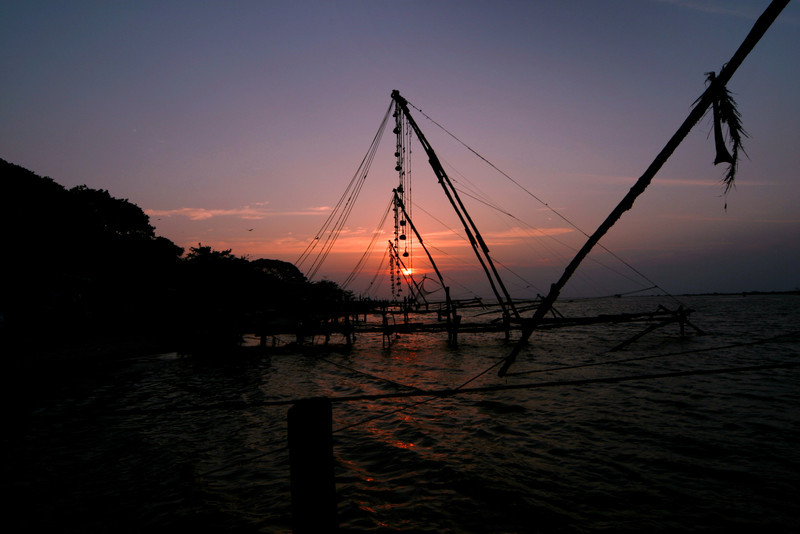 The sun sets behind the famous Chinese fishing nets